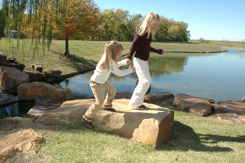 Wait for me. Two beautiful little blond sisters play and explore a nature area in a park. Spending time with family and being together. Two little girls holding royalty free stock images