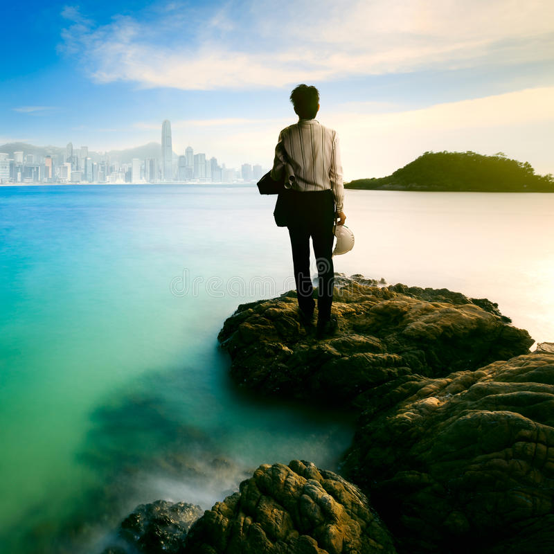 Wait for opportunity. Businessman standing in front of a coastline and observing a cityscape on the background stock photo
