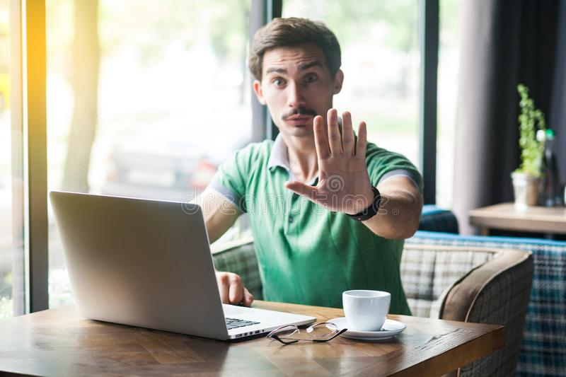 Wait, Stop! Young serious businessman in green t-shirt sitting, working on laptop, looking at camera, showing stop sign gesture stock photography