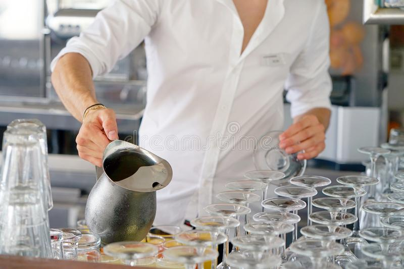 The waiter in the bar pouring juice from iron pitcher, shallow dof stock image
