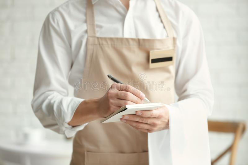 Waiter in beige apron writing down an order in a cafe. Close up stock images