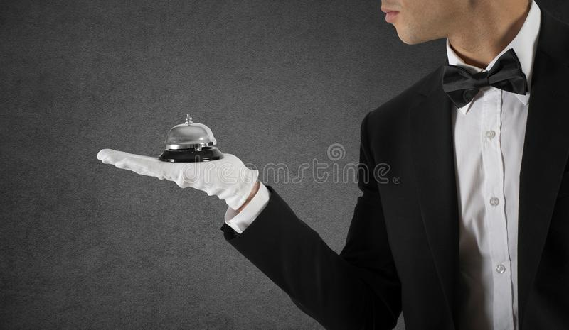 Waiter with bell in hand. Concept of first class service in your business. Waiter holds with bell in hand. Concept of first class service in your business stock photography