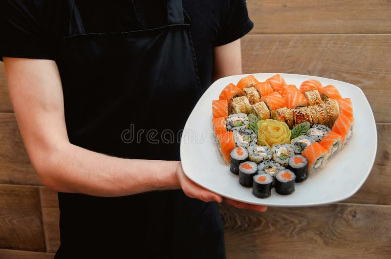 Waiter in a black apron holds dishes with sushi set in the shape of a heart for Valentine`s Day. Gallant Waiter in a black apron holds dishes with sushi set in stock image