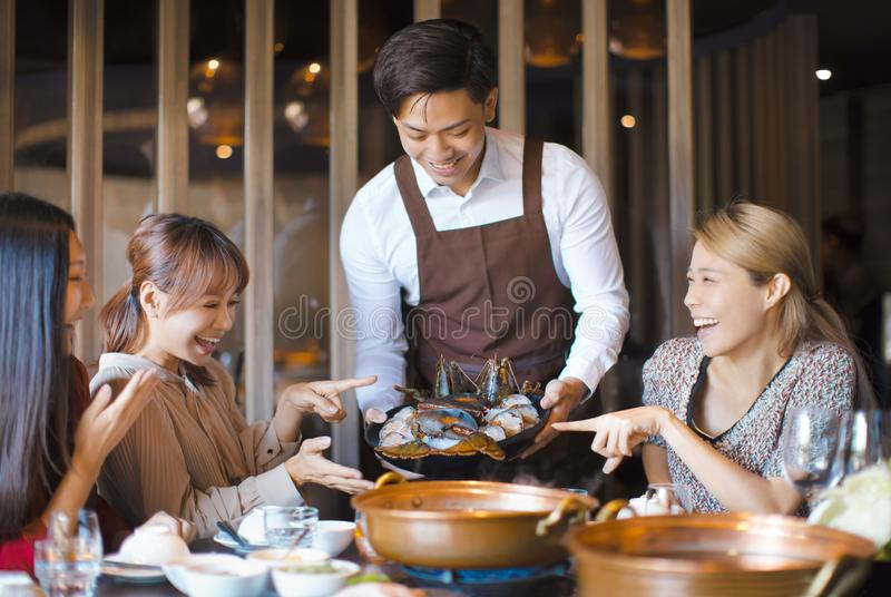 Waiter  bring  seafood  and serving group of friends in restaurant royalty free stock photo