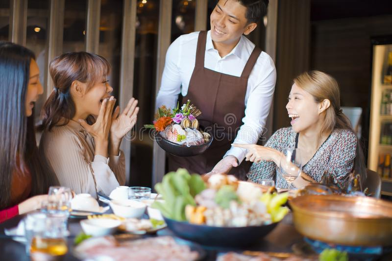 Waiter  bring  seafood  and serving group of friends in restaurant stock photography