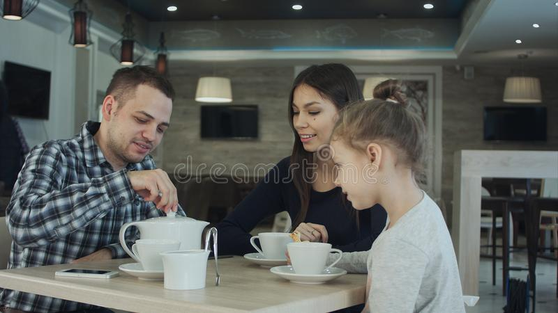 Waiter bringing tea and sugar to young family in cafe. stock photo