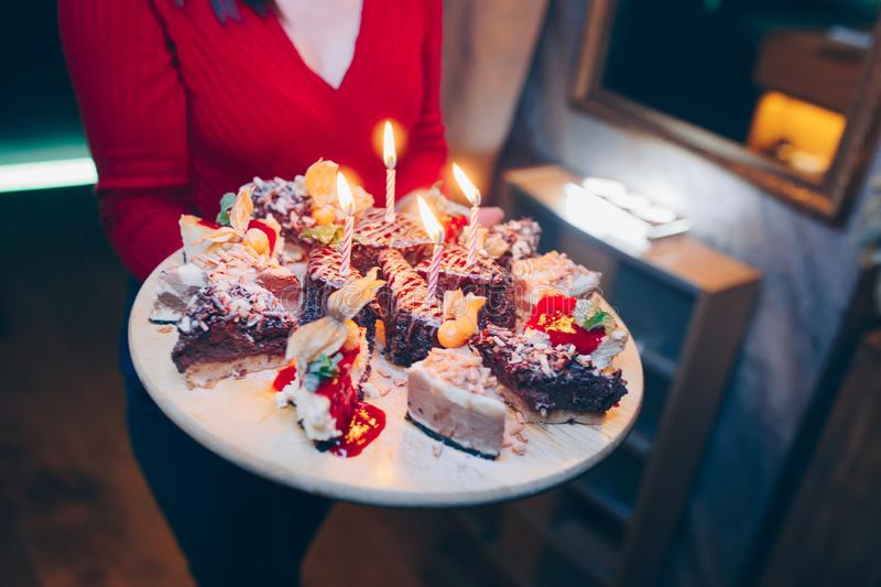 Waiter brings Birthday cake with candles in motion , bright lights at restaurant, close up view.Celebrating birthday day. Toned im. Age. Selective focus. Design stock images