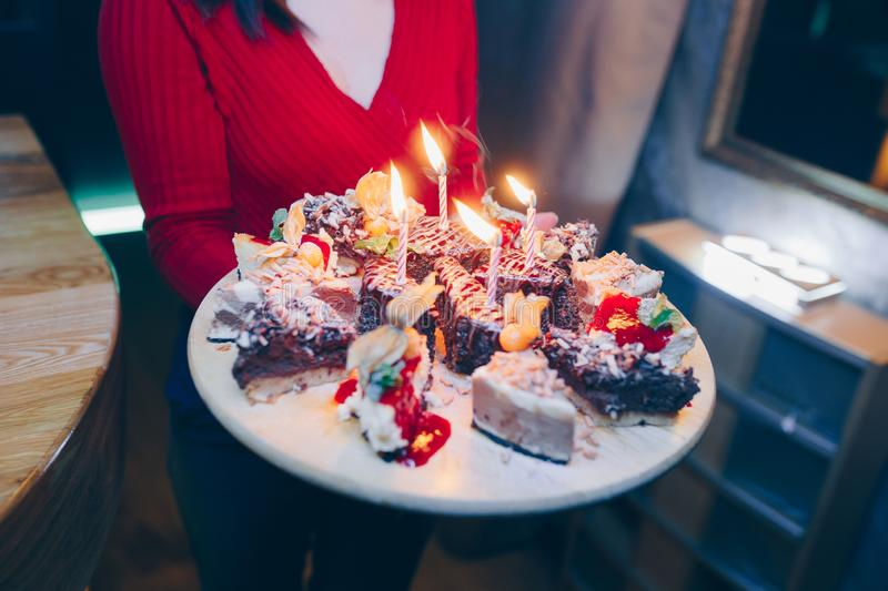 Waiter brings Birthday cake with candles in motion , bright lights at restaurant, close up view.Celebrating birthday day. Toned im. Age. Selective focus. Design royalty free stock photography