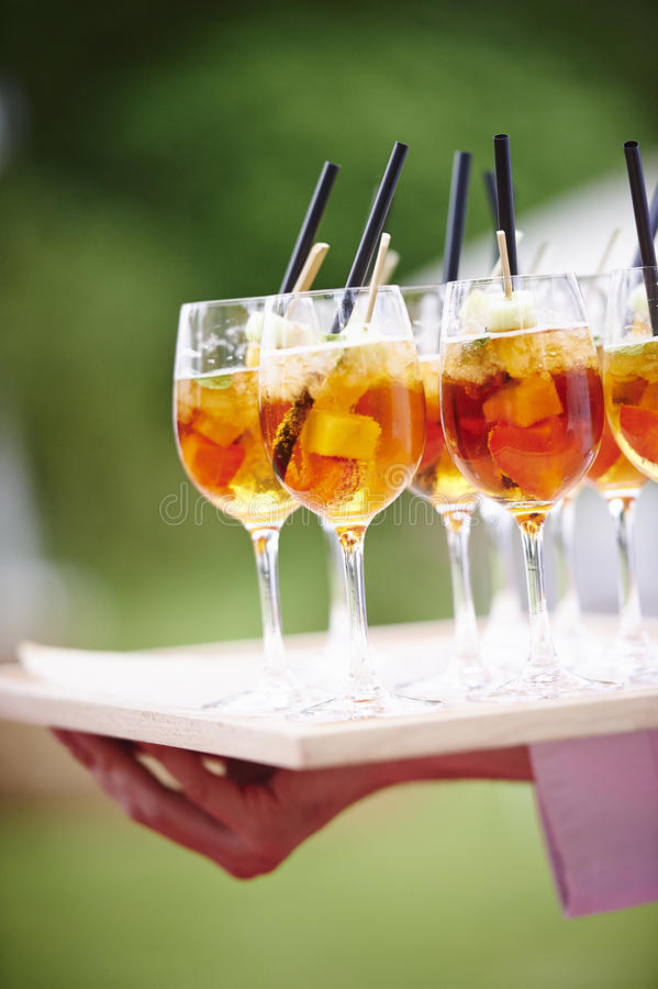 Waiter carrying tray of cocktails with straws. Waiter carrying a tray of tropical cocktails with fruit and straws stock images