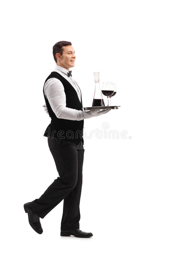Waiter carrying a tray with wine royalty free stock photography