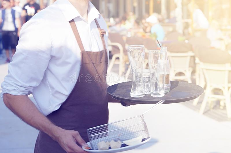 Waiter cleaning the table in a restaurant. A waiter is holding a tray with dirty dishes and leftover food in a cafe on the beach. Waiter cleaning the table in a royalty free stock image