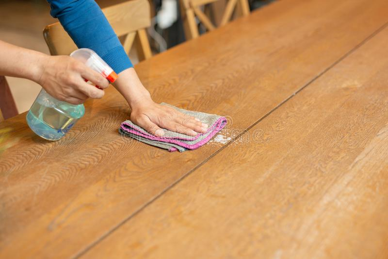 Waiter cleaning the table with spray disinfectant on table in restaurant. Waiter cleaning the table with spray disinfectant on table in restaurant stock photos