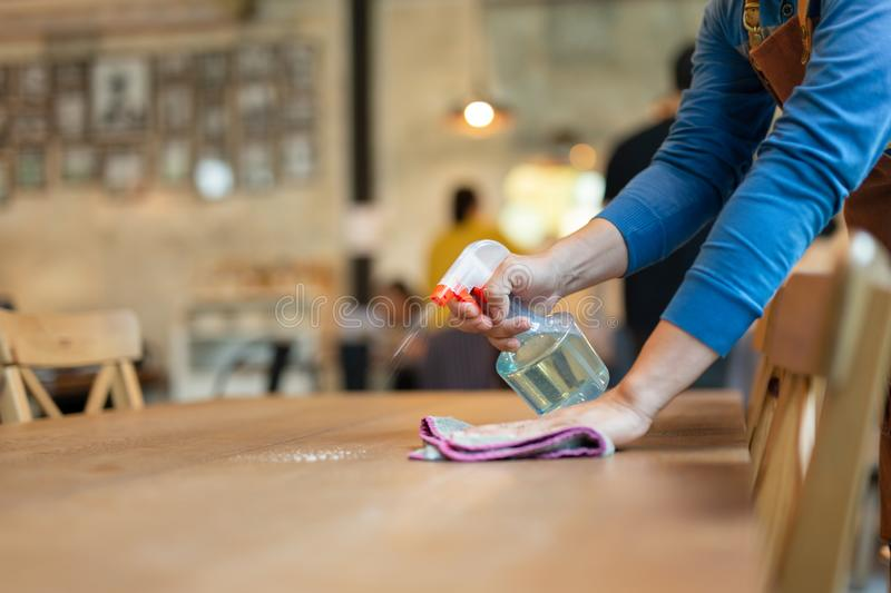 Waiter cleaning the table with spray disinfectant on table in restaurant.  royalty free stock photo