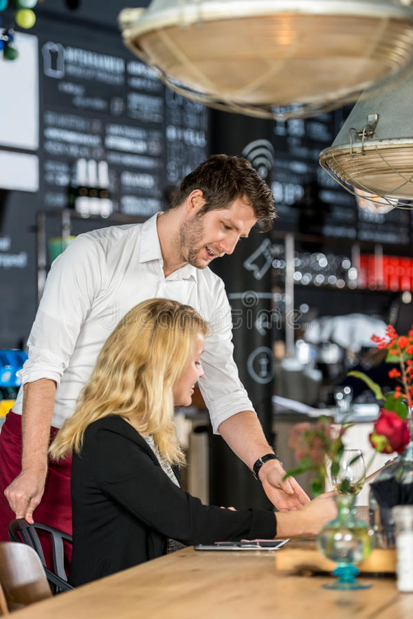 Waiter Discussing Menu With Customer In Cafe. Young waiter discussing menu with female customer at table in cafe stock photos