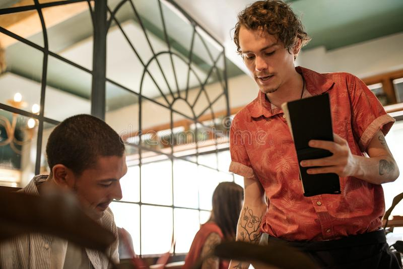 Waiter explaining the menu to a smiling restaurant customer. Young waiter taking an order from a young men reading a menu at a table in a trendy restaurant royalty free stock images