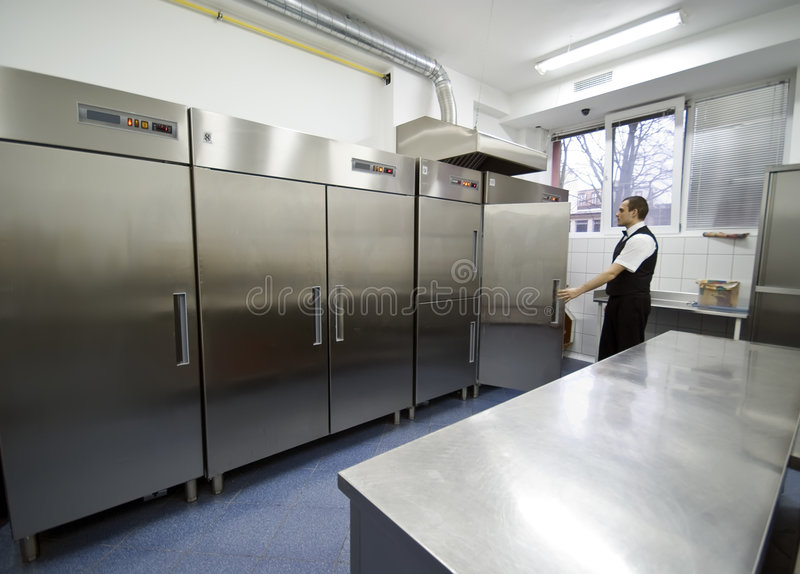 Waiter and fridges. A waiter in a kitchen looking into one of many refrigerators stock image