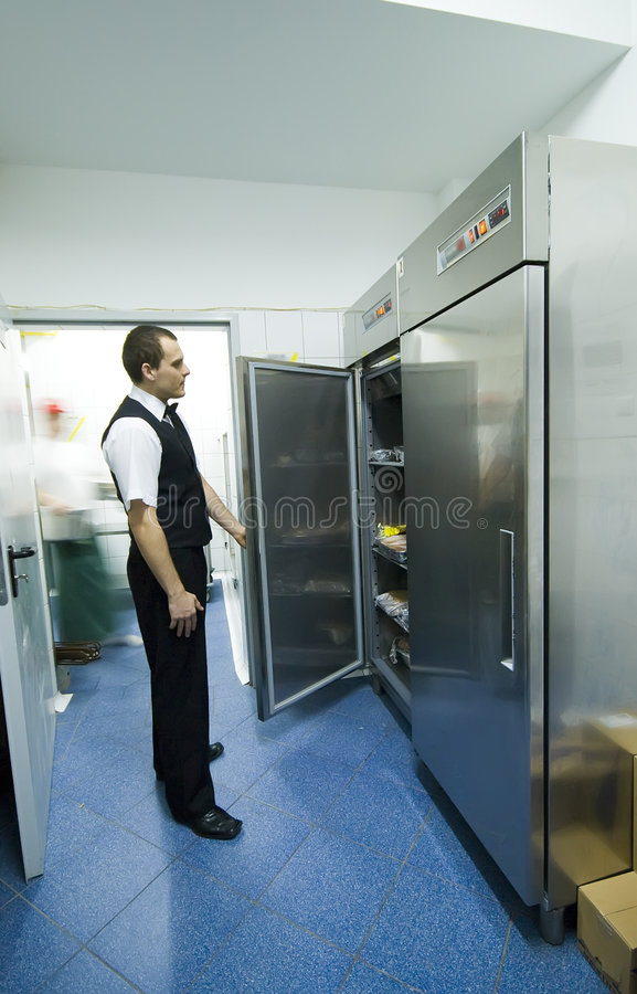 Waiter and fridges. A waiter in a kitchen looking into one of many refrigerators stock photography