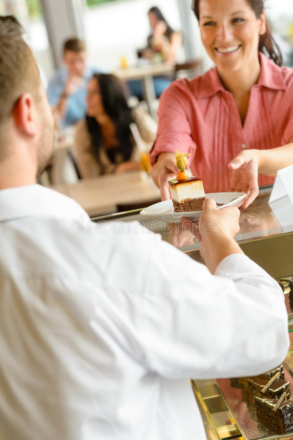 Waiter giving woman cake plate at cafe stock photo