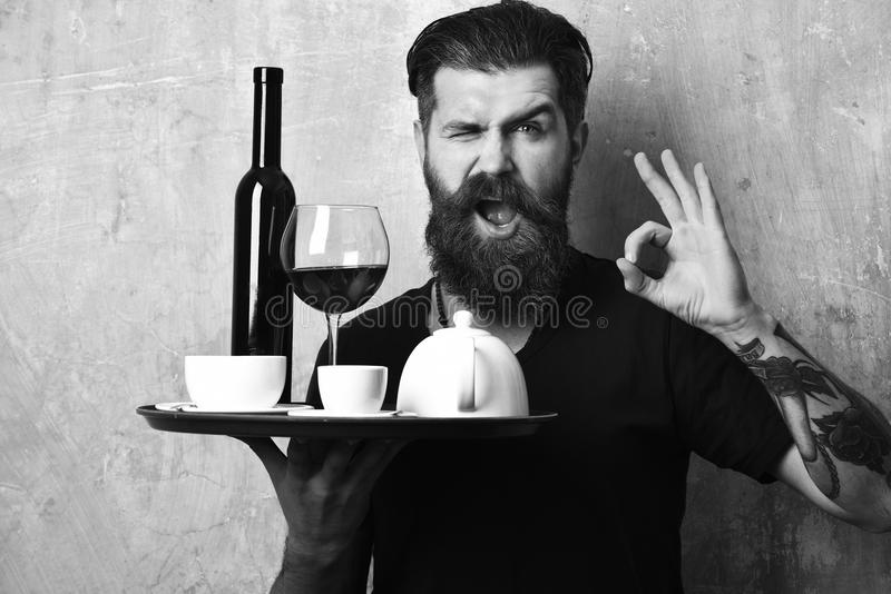 Waiter with glass and bottle of wine by tea on tray. Man with beard holds various drinks on beige wall background. Barman with flirty face serves wine and tea stock photography