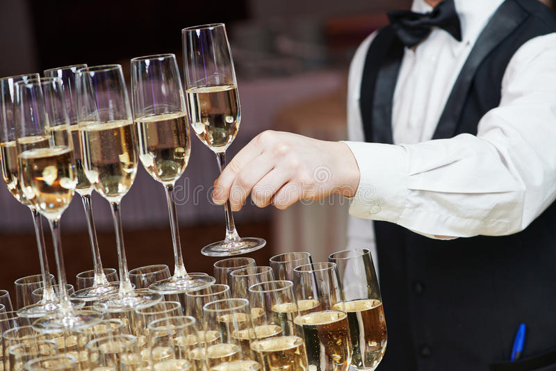 Waiter with glass of champagne. Waiter hand with glass of champagne over pyramid during catering at party royalty free stock photography