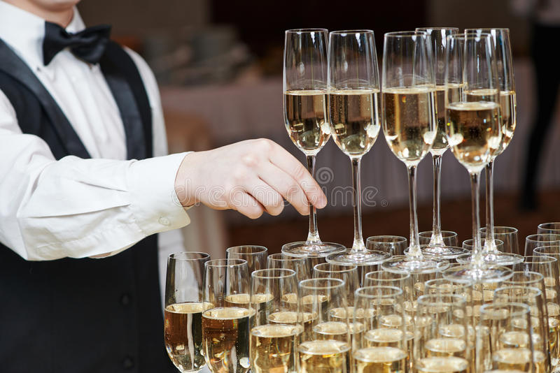 Waiter with glass of champagne. Waiter hand with glass of champagne over pyramid during catering at party stock photos