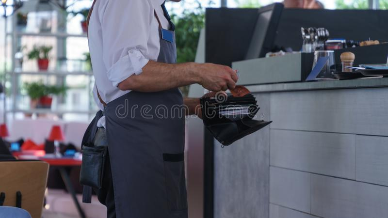 A waiter in a gray shirt with cash standing at the checkout stock photos
