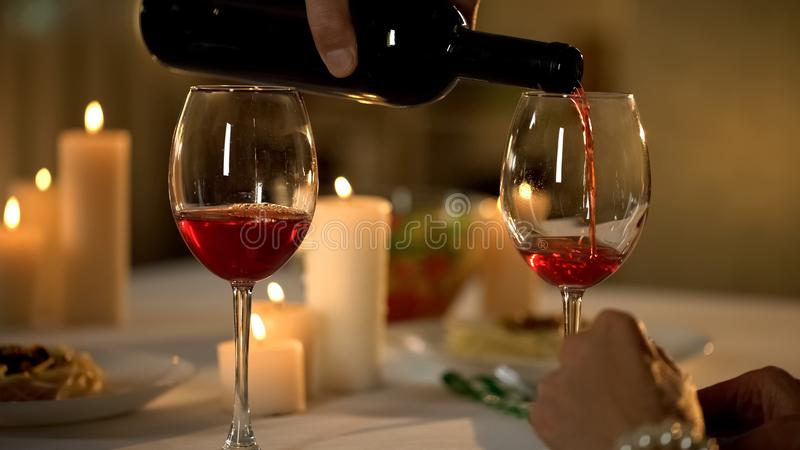 Waiter hand pouring wine in glass, traditional alcoholic beverage for dinner. Stock photo stock photo