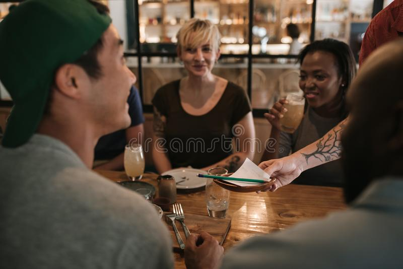 Waiter handing the bill to smiling customers in a bar stock image