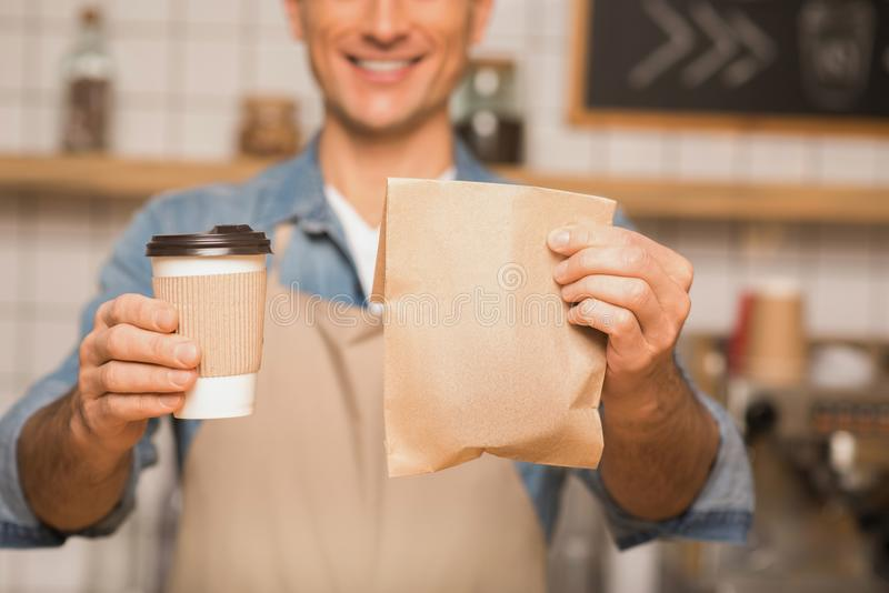 Waiter holding coffee to go and take away food. Close up of waiter holding coffee to go and take away food in cafe stock photography