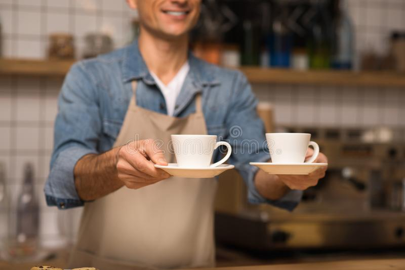 Waiter holding cups of coffee. Close up of smiling waiter holding two cups of coffee royalty free stock image