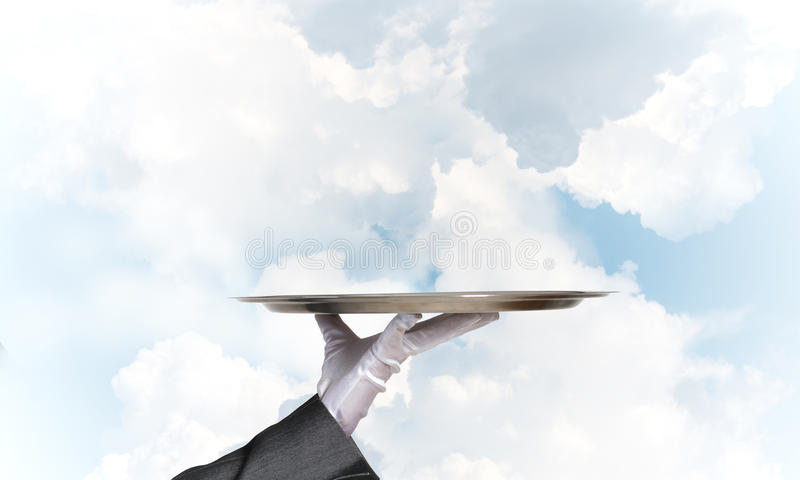 Waiter holding empty silver platter ready for product or item placement. Butler hand in white glove presenting empty tray stock photo