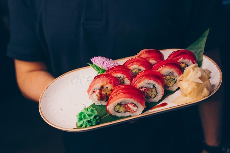Waiter holding Philly Sushi plateau, New York California dining restaurant. Delicious Philadelphia flesh seaweed and ginger. Rolls stock images