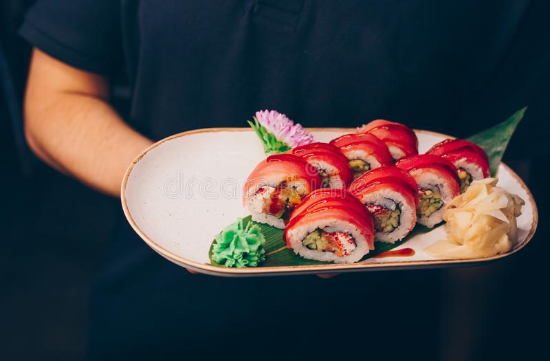Waiter holding Philly Sushi plateau, New York California dining restaurant. Delicious Philadelphia flesh seaweed and ginger. Rolls. Served on the white plate in royalty free stock photos