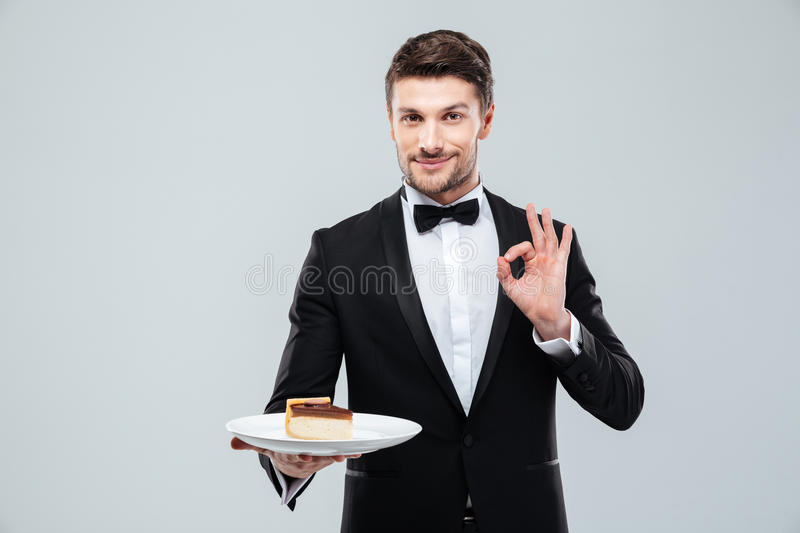 Waiter holding plate with cake and showing ok sign royalty free stock images