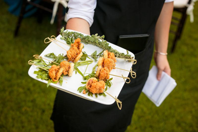 A waiter holding a plate of mini fried chicken and waffles - wedding catering series. Waiter holding a plate of mini fried chicken and waffles - wedding catering stock image