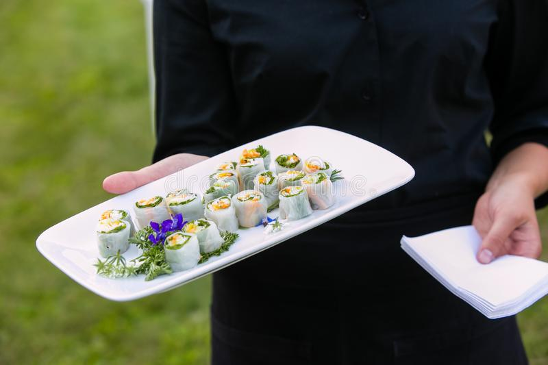 A waiter holding a plate of spring rolls - wedding catering series. Waiter holding a plate of spring rolls - wedding catering series stock photo