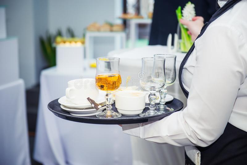 The waiter holding tray with dirty dishes after guests of the event. Catering Service at business meeting, party, weddings. Food C royalty free stock images