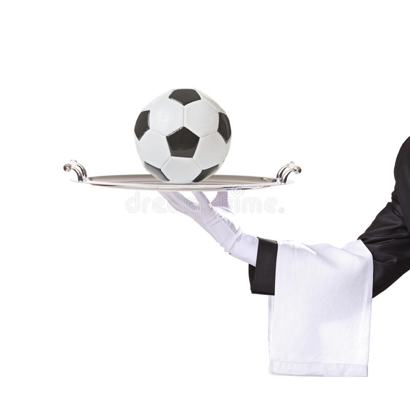Waiter holding a tray with a football on it royalty free stock image