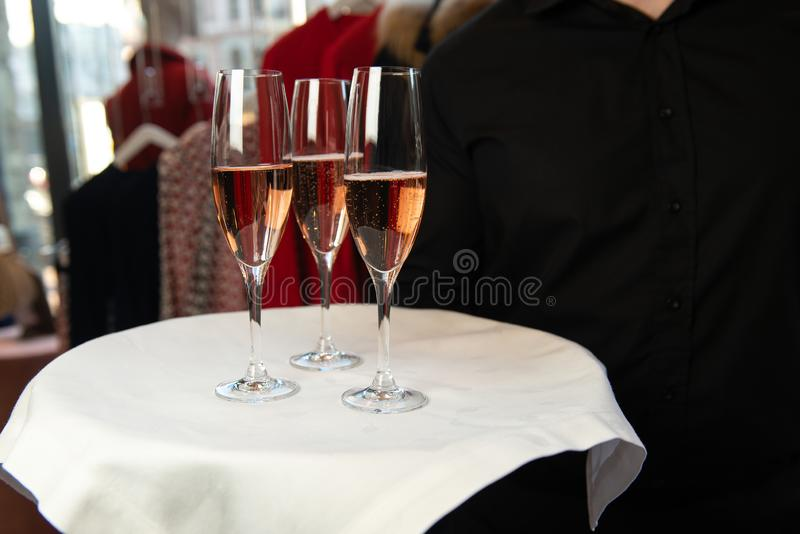 Waiter holding tray with rose champagne in wine glasses. royalty free stock photos