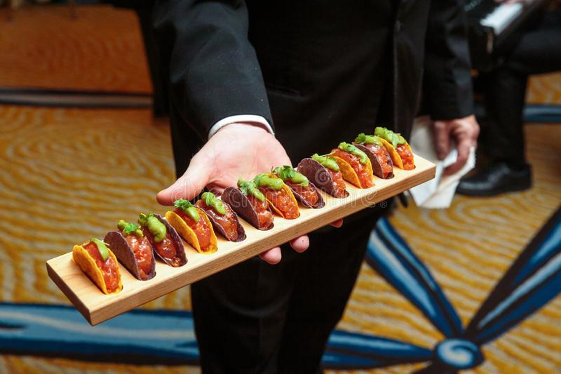 A waiter holding a wooden platter full of taco appetizers - wedding catering series royalty free stock image