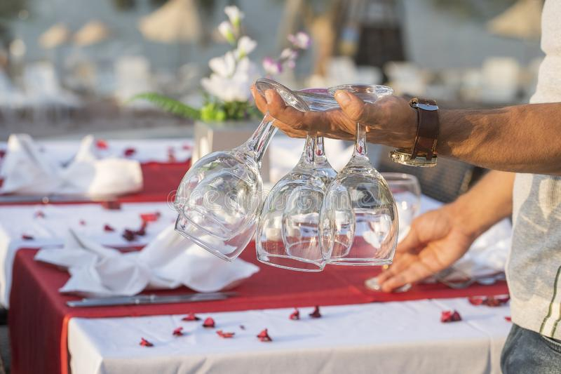 The waiter holds wine glasses in his hand and sets the table in a restaurant . Nice dining table set with arranged silverware and. Napkins for dinner, Turkey royalty free stock images