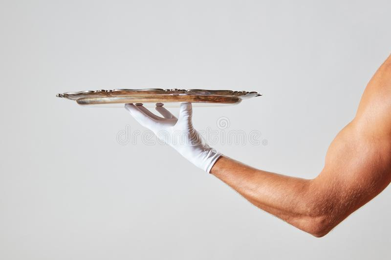 Waiter with muscular hand in a white glove holding a metal empty tray on a white background. Muscular hand of waiter in a white glove holding a silver vintage royalty free stock photo