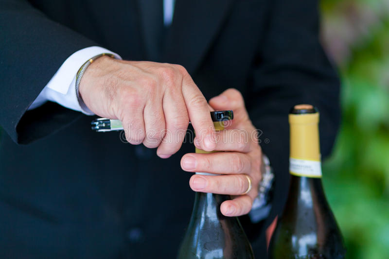 Waiter opening a bottle of white wine royalty free stock photography