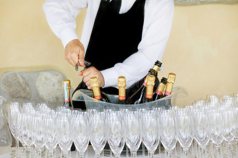 Waiter opening a bottle of white wine stock photos