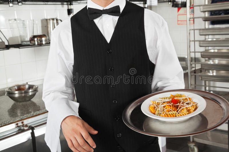 Waiter With Pasta Dish. Midsection of waiter with pasta dish in commercial kitchen royalty free stock photography