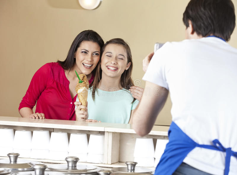 Waiter Photographing Happy Mother And Daughter With Ice Cream royalty free stock photo