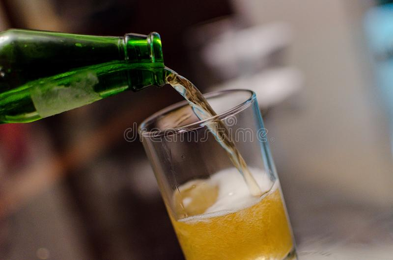 Waiter pouring beer, glass of a cold drink , Oktoberfest autumn holiday stock image