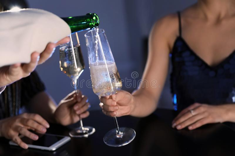 Waiter pouring champagne from bottle into woman`s glass at bar royalty free stock photography
