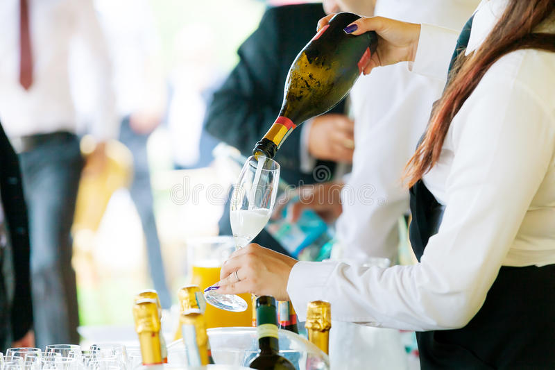 Waiter pouring champagne stock photos