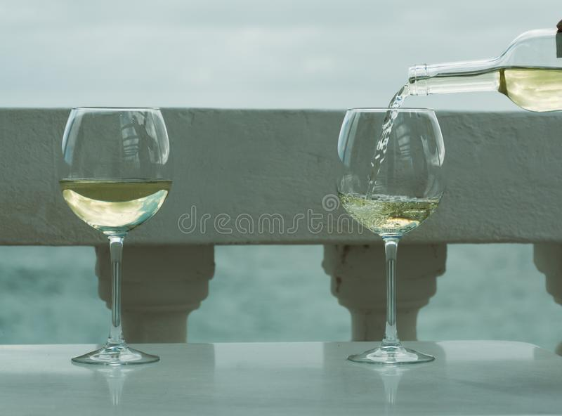 Waiter pouring glass of white wine on outdoor terrace with sea v. Waiter pouring glass of white wine on outdoor terrace with beautiful romantic sea view royalty free stock photos